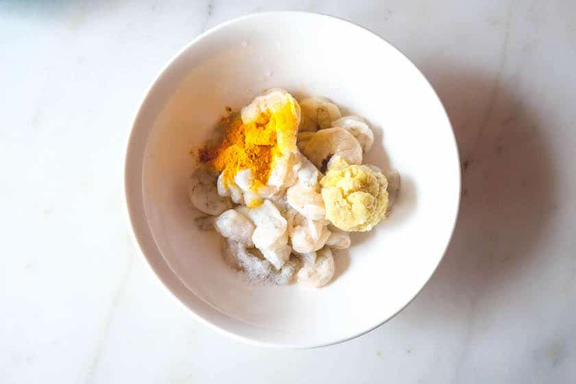 Firstly clean and wash the prawn, devein them. Add ginger garlic paste, turmeric powder, and salt in an bowl