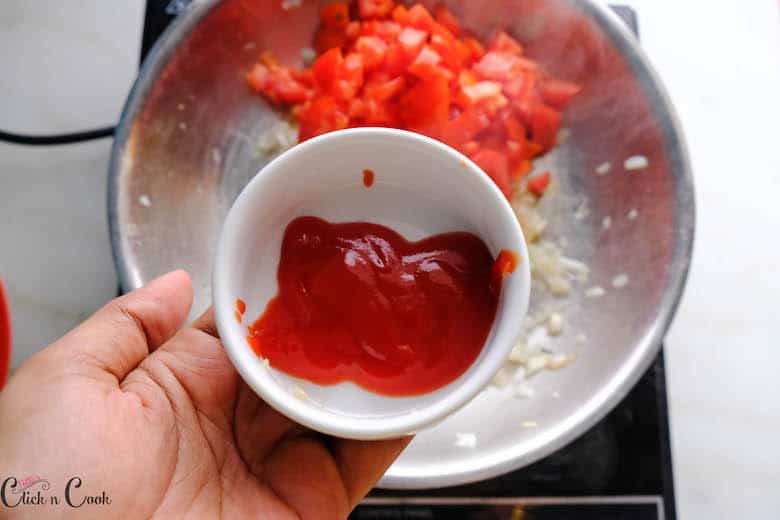 tomato sauce is being added to chopped tomatoes cooked in saute pan