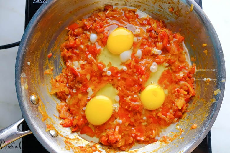 eggs are added to the spaces in onion-tomato masala in saute pan