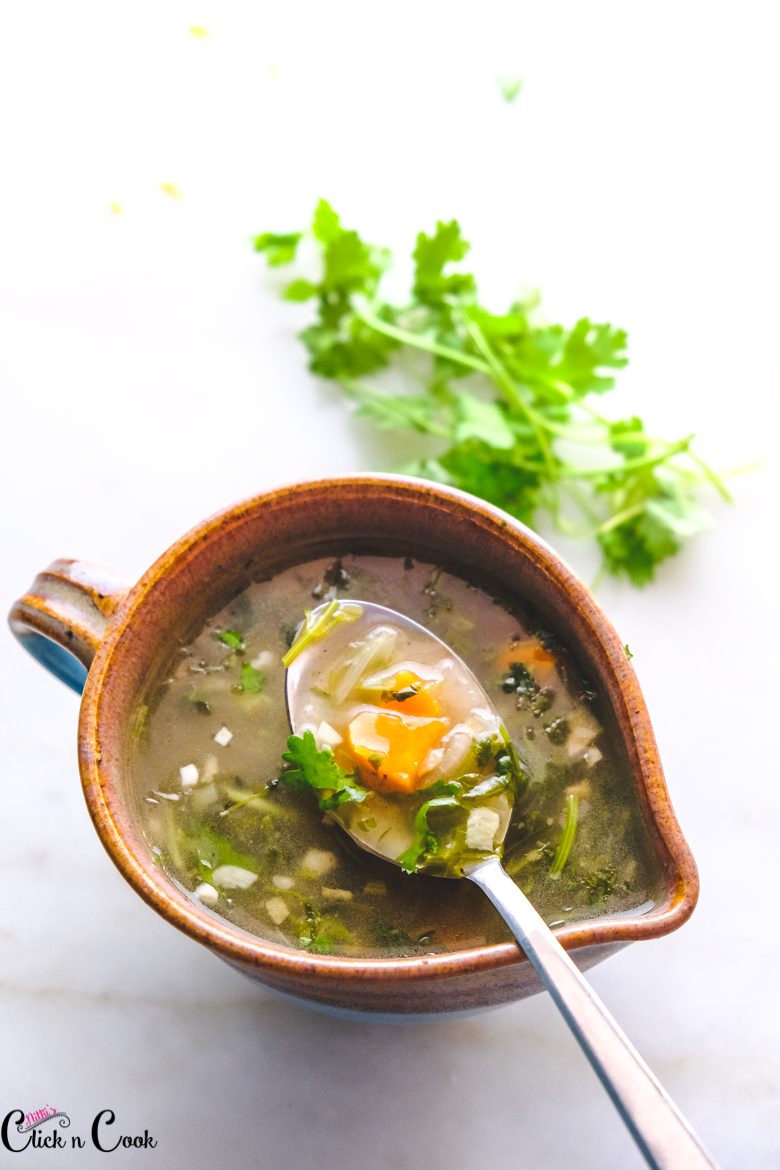 a spoon of lemon and coriander soup is in serving bowl