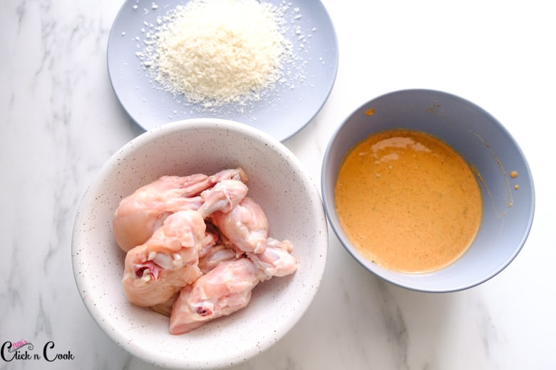 chicken wings in white bowl, marinade in grey bowl and panko bread crumbs are in grey plate