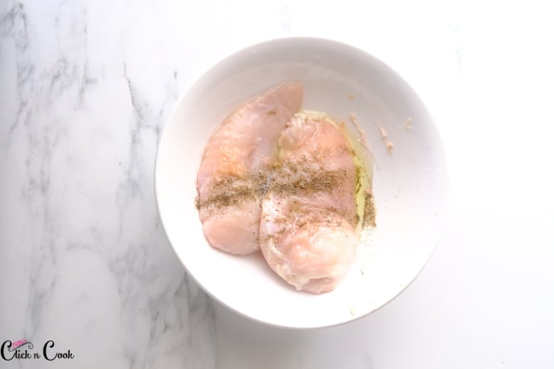 chicken breast with salt and pepper are taken in white bowl