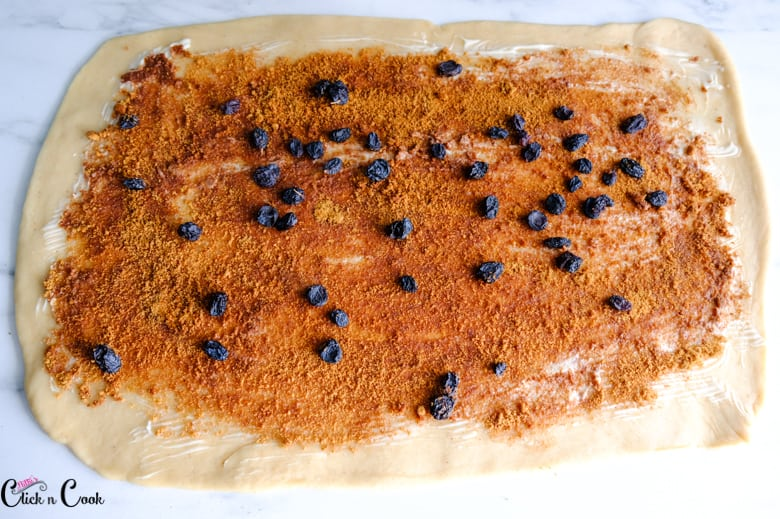 cinnamon powder, brown sugar and raisin are spread over the dough