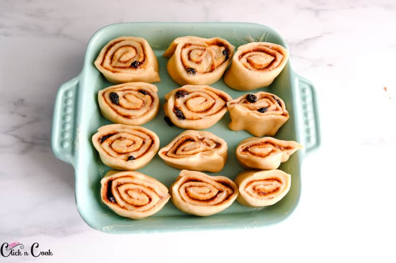 rolled cinnamon rolls recipe in blue baking tray