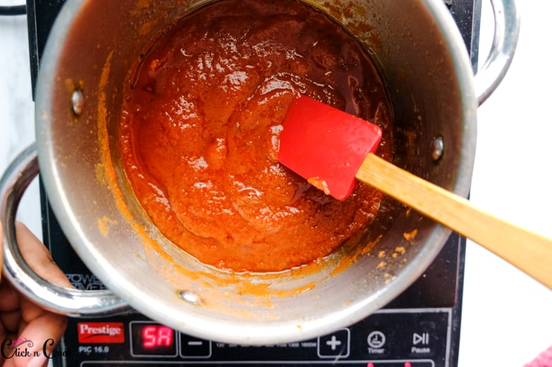 barbecue sauce sauce in the sauce pan is being stirred using spatula